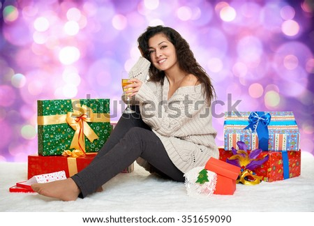 beautiful young girl with a glass of champagne and gift boxes, colorful bokeh background - stock photo