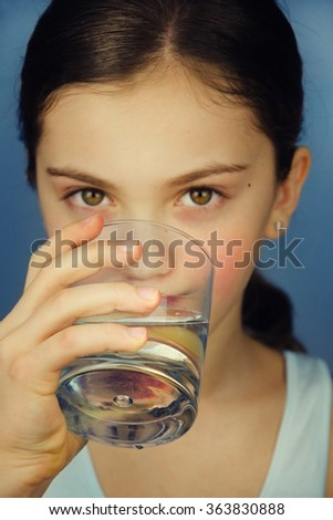 Beautiful young girl with a glass of water.