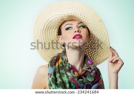 beautiful young girl with a hat bright makeup with color beautiful expensive scarf at the neck on white background in Studio - stock photo