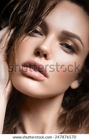 Beautiful young girl with a light natural make-up. Beauty face. Picture taken in the studio on a black background. - stock photo