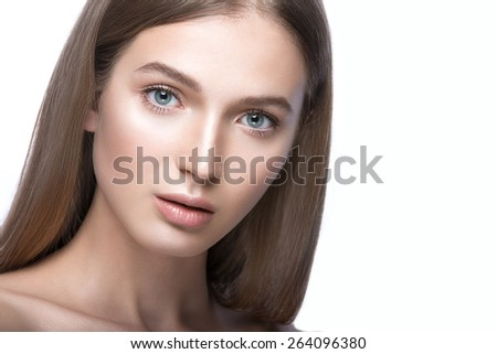 Beautiful young girl with a light natural make-up. Beauty face. Picture taken in the studio on a white background. - stock photo