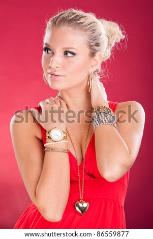 Beautiful young girl with a lot of jewelry on a red background - stock photo