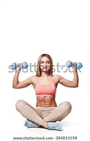 Beautiful young girl with a sports body with dumbbells on a white studio background