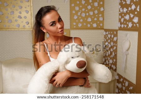 Beautiful young girl with big breasts, full lips, straight hair, in a candid white underwear, athletic, tanned, with a white teddy bear in the interior of the hotel on the background of white and gold - stock photo