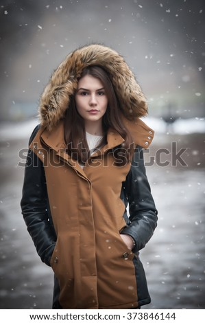Beautiful young girl with brown coat trimmed with gray fur enjoying the winter scenery in park. Teenage girl with black leather sleeves coat posing in winter concept. Young female bright cold day