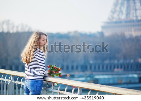 Beautiful young girl with bunch of red tulips near the Eiffel tower