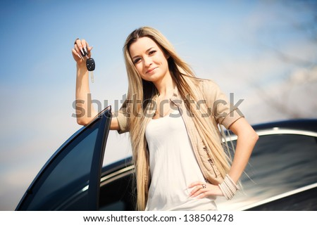 Beautiful young girl with car key in hand - stock photo