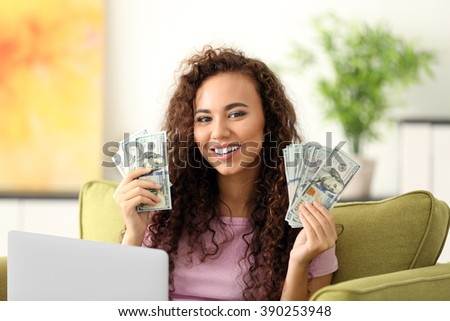 Beautiful young girl with cash and laptop on armchair - stock photo