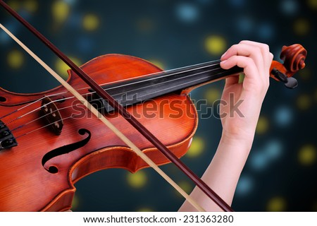 Beautiful young girl with classical violin on bright background - stock photo