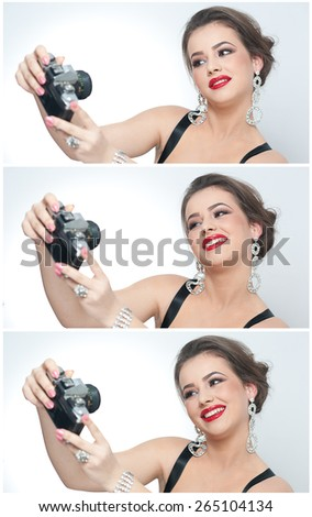 Beautiful young girl with creative make-up and hair style taking photos of herself with a camera. Fashionable attractive woman taking a self portrait. Selfie, indoor, horizontal, over white. - stock photo