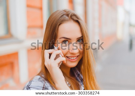 Beautiful young girl with creative make-up and hair style taking photos of herself with a camera. Fashionable attractive woman taking a self portrait. Selfie, indoor, horizontal, over white wall  - stock photo