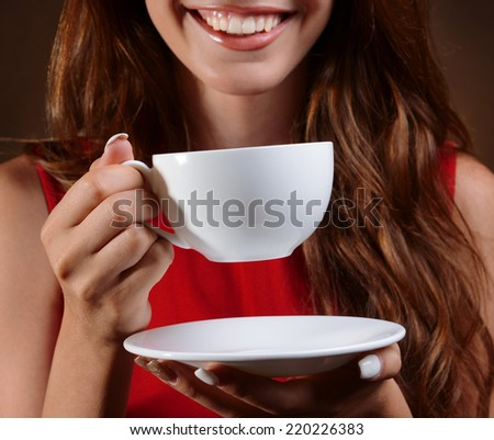 Beautiful young girl with cup of coffee on brown background