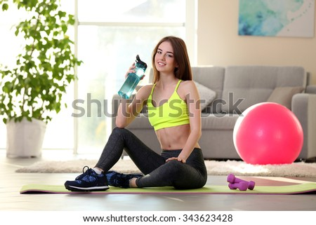 Beautiful young girl with fit ball at home - stock photo