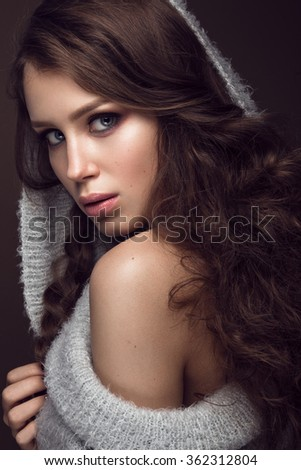 Beautiful young girl with gentle make-up in warm sweater and long straight hair. Beauty face. Studio portrait