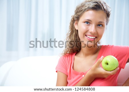 beautiful young girl  with green apple smiles - stock photo