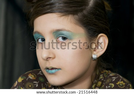 Beautiful young girl with green flashy eye make up