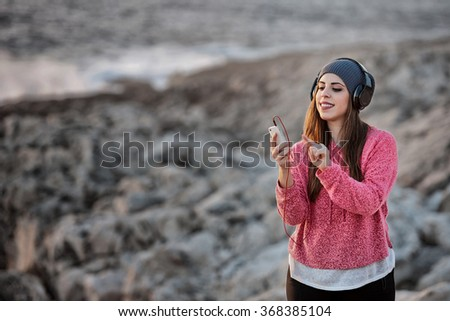 Beautiful young girl with headphones and smart phone at the beach