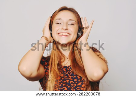 Beautiful young girl with headphones listening music - stock photo