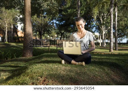 Beautiful young girl with laptop or tablet in park
