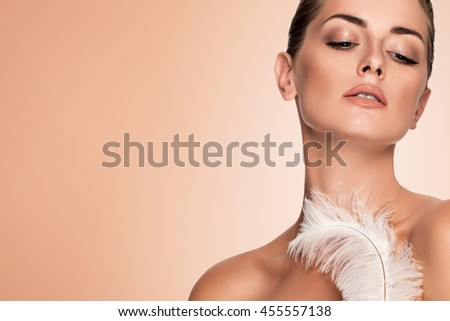 Beautiful young girl with large white feather. clean soft body products. Beauty Portrait. Woman Touching. Perfect Fresh Skin. Youth and Skin Care Concept. Studio shot. Isolated on brown background - stock photo