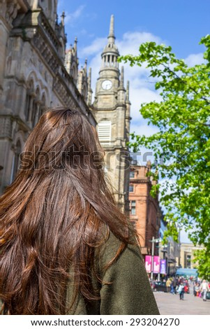 Beautiful, young girl with long brown hair standing with her back to the camera in the streets Glasgow, Scotland  - stock photo