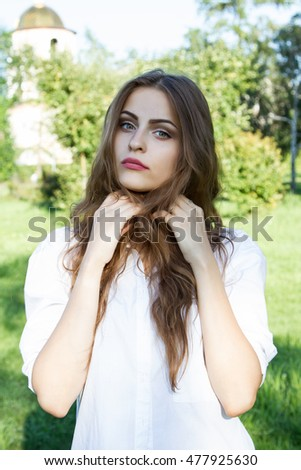 Beautiful young girl with long hair and wearing a white shirt in the summer park