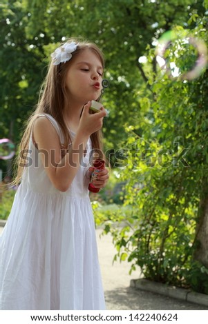Beautiful young girl with long hair playing in the streets and blow bubbles