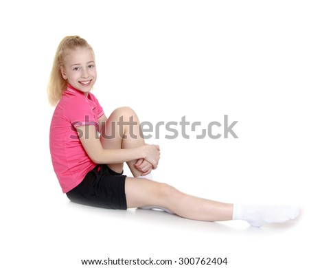 Beautiful young girl with long, thick blond tail in a pink t-shirt with short sleeves and black shorts. Girl sitting on the floor stretching out a leg , the other leg girl holding hands-Isolated on - stock photo