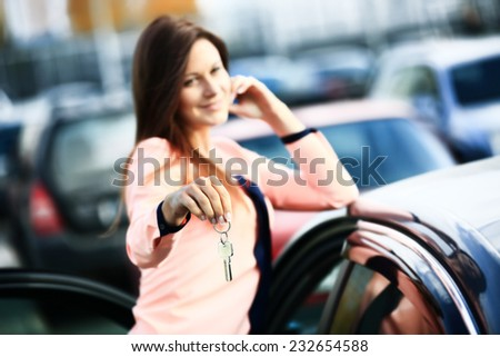Beautiful young girl with new car key in hand - stock photo