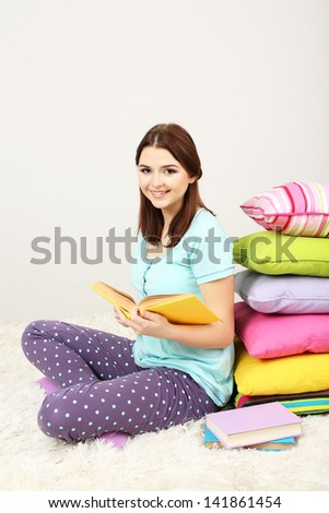 Beautiful young girl with pillows and books in room