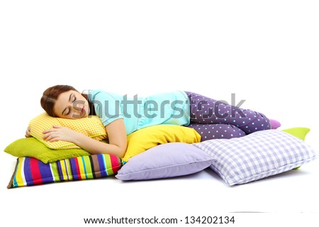 Beautiful young girl with pillows isolated on white