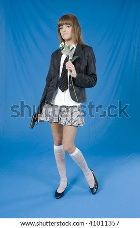 Beautiful young girl with pistol and flower in a hands on blue background