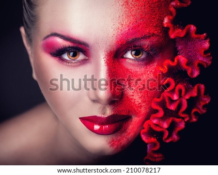 Beautiful young girl with professional fashion makeup with flower on a black background