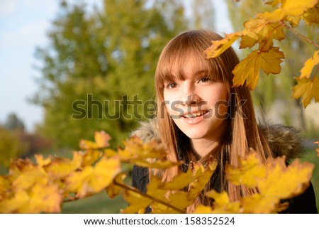 Beautiful young girl with red hair, against the backdrop of golden autumn