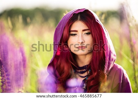 Beautiful young girl with red hair in a romantic purple raincoat sitting in a field at sunset lupine summer, closeup portraits