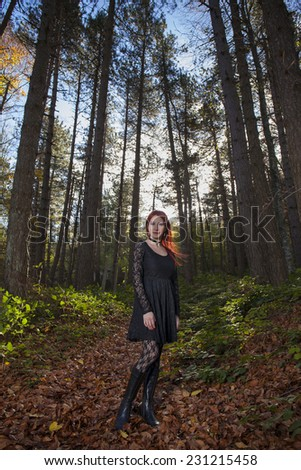 Beautiful young girl with red hair in gothic clothing in a forest with tall trees  and blue sky background - stock photo