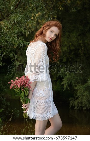 Beautiful young girl with red long hair in a white dress and flowers in the hands on a background of green trees.