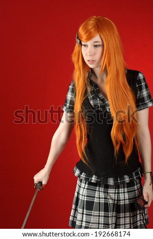 Beautiful young girl with red-orange hair with katana sword - stock photo