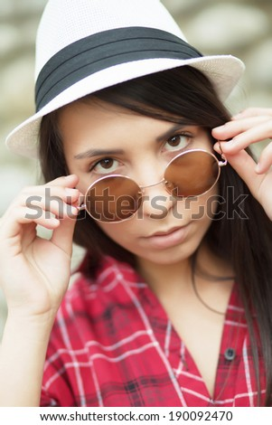 Beautiful young girl with round sunglasses and white hat