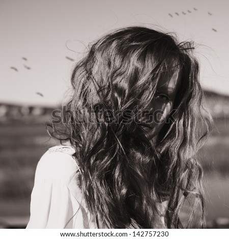 beautiful young girl with shaggy hair in a mysterious space - stock photo