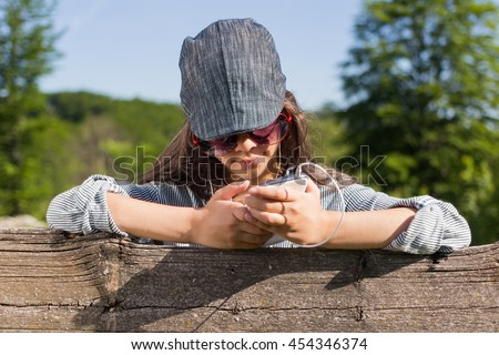 Beautiful young girl with smart phone and headphones listening to music outdoors on sunny spring day.Countryside background. - stock photo