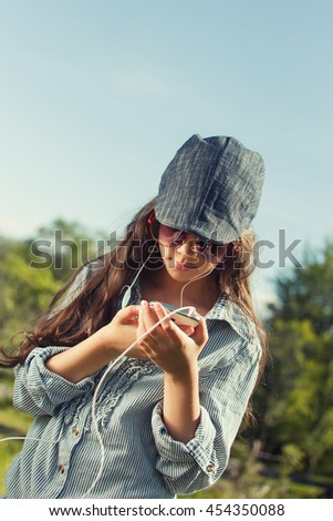 Beautiful young girl with smart phone and headphones listening to music outdoors on sunny spring day. Cross process,countryside background - stock photo