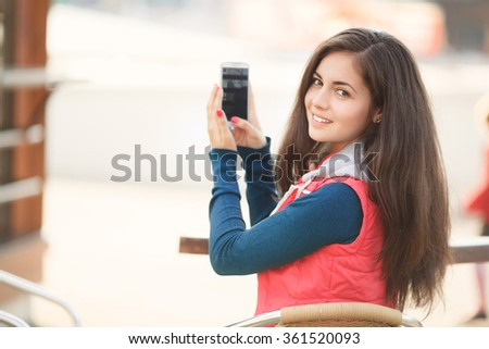Beautiful young girl with smartphone outdoors, smiling woman taking selfie on phone, pretty female with mobile phone at city street, instagam filter like soft grain and tonality, series