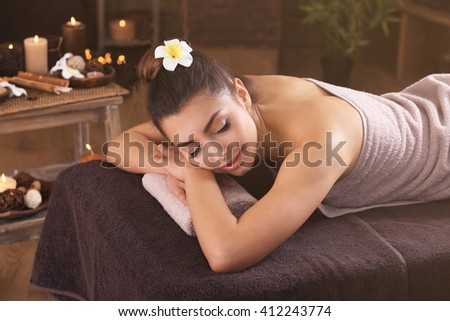 Beautiful young girl with towel lying on massage table in spa salon - stock photo