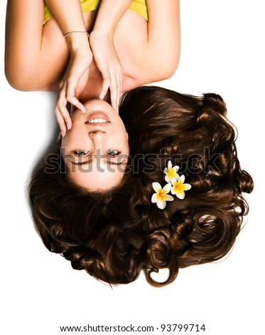Beautiful young girl with voluminous hair and plumeria - stock photo