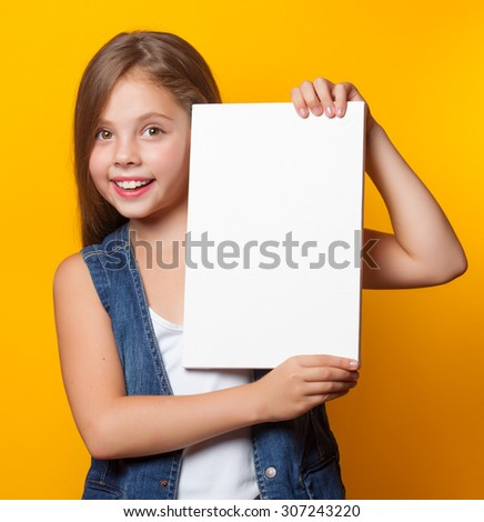 Beautiful young girl with white board on yellow background. - stock photo