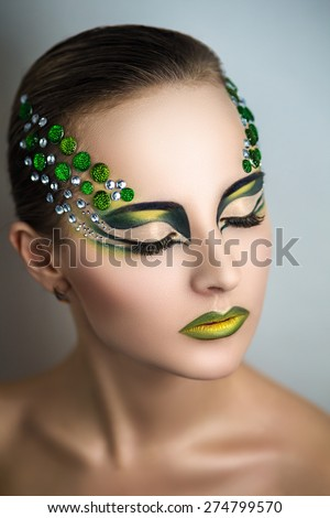 Beautiful young girl, woman, lady, predator, dragon, witch, alien, fairy tale. Mythical, stylish look. Bright creative makeup, perfect skin, expressive eyes, color, yellow, green, gems, crystals, art - stock photo