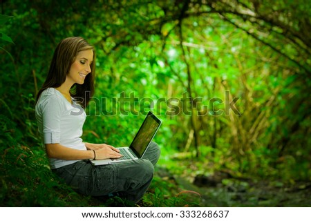 Beautiful young girl working with laptop enjoying excellent connectivity in the middle of the jungle
