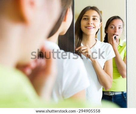 Beautiful young girls doing make-up in front of the mirror at home