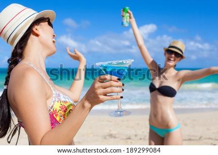 Beautiful young girls having fun at the beach in Hawaii. Happy young teen girls dancing at the beach. - stock photo